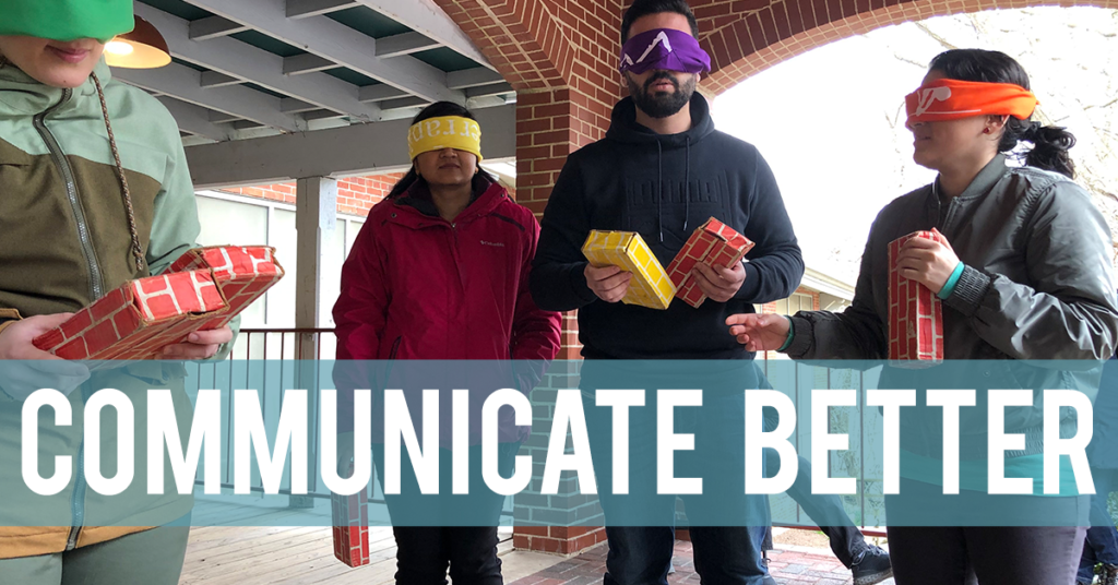 Blindfolded people holding colorful plastic bricks and awaiting instructions. The words Communicate Better are superimposed on the image.