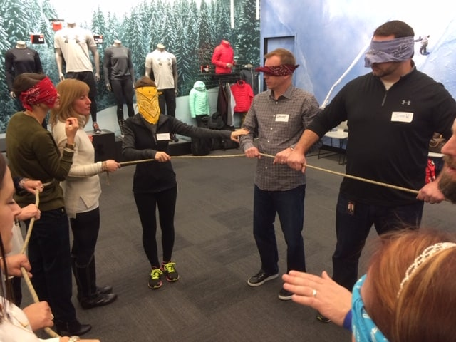 A group of blind folded people attempt to create shapes with a rope.