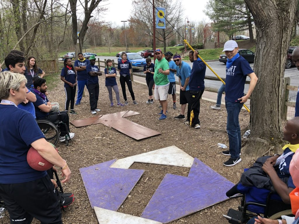 """A group forms a """"T"""" shape during a team building exercise."""