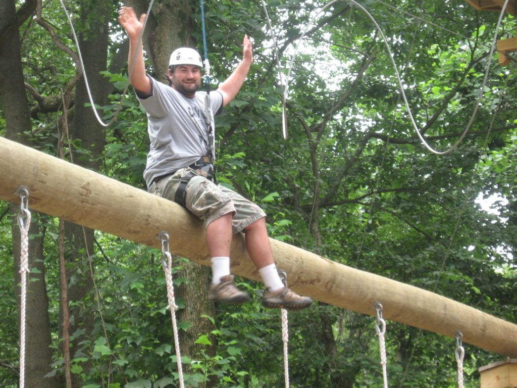 Man sitting on a log high in the air on a ropes course.
